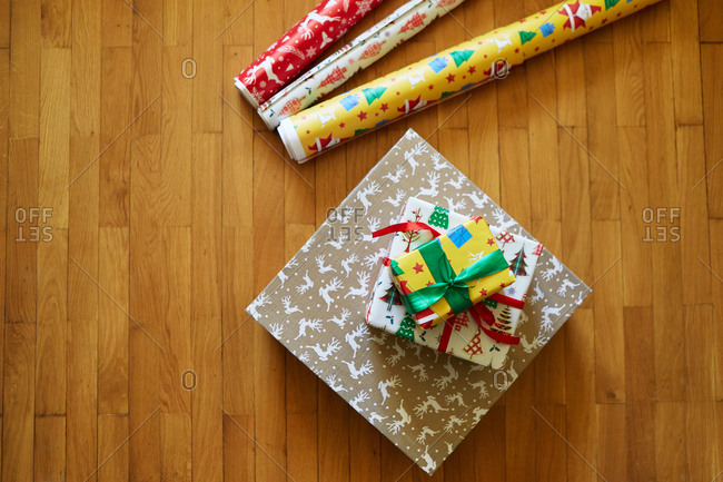 Colorful Christmas presents in a pile on hardwood floor beside rolls of wrapping paper