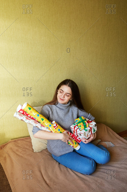 A happy young woman holding a stack of Christmas gift and rolls of wrapping paper