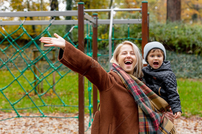 Happy mother with a child on a playground in autumn