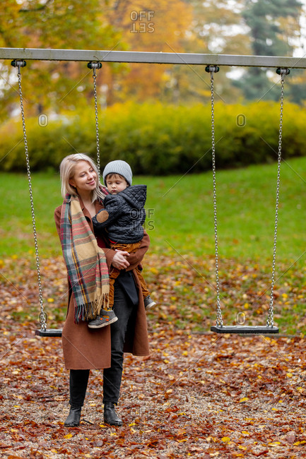 Mother with a child by swings on playground in autumn