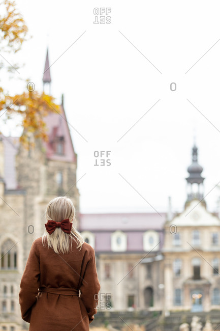 Rear view of blonde in coat and bow with old castle on background