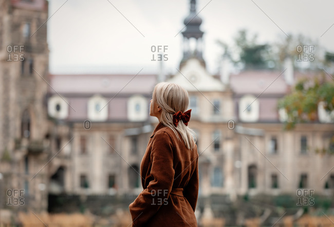 Blonde in brown coat and red bow with old castle in the background