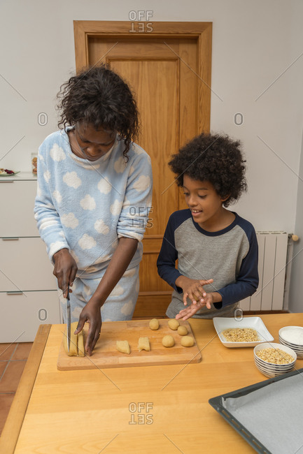 African single parent family preparing Panellets, typical pastries of Catalonia, with ground almond, pine nuts, grated coconut and sugar. Food concept