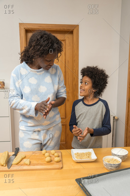 African single parent family preparing cookies ,with ground almond, pine nuts, grated coconut and sugar