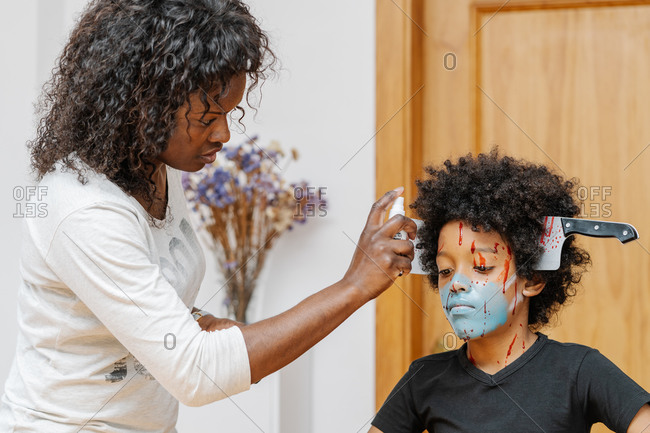 Mother painting face of son in living room. Halloween and carnival concept