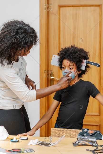 Mother painting her son's face for a costume party. Halloween and carnival concept