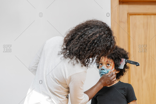 Mother Applying Face Paint her son for Halloween Costume. Halloween and carnival concept