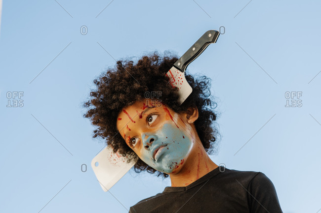 Portrait of afro boy with painted blue mask on his face. Halloween and carnival concept