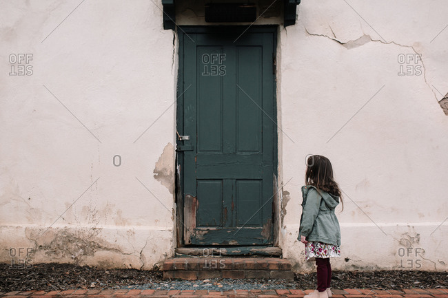 Little girl looking at an old home's exterior with a dark green door