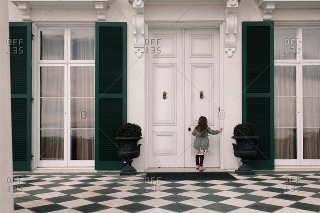 Rear view of a little girl standing in front of a large white double door on a home with green shutters