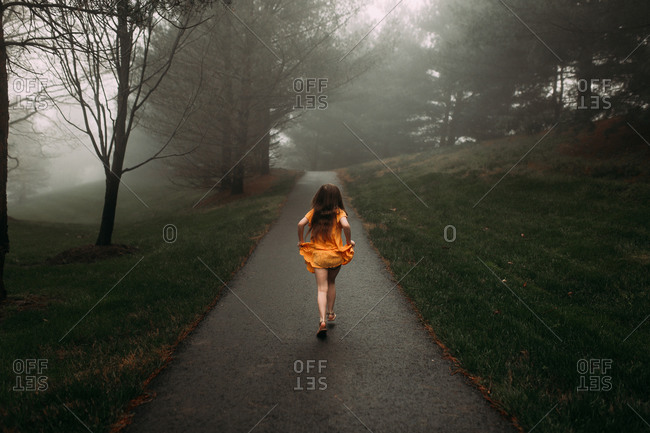 Rear view of a young girl walking down a mysterious path