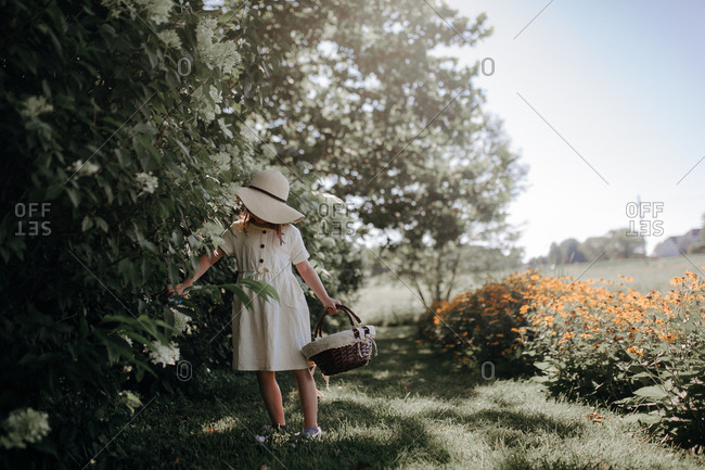 Young girl walking in a summer field with flowers wearing a white sun hat and matching dress