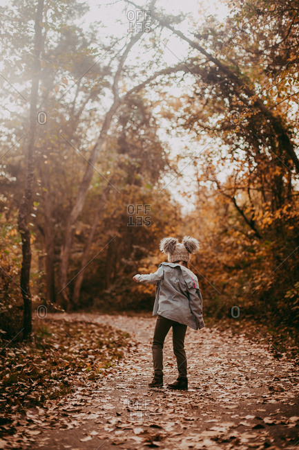 Little girl walking on a path in a park covered in fallen leaves