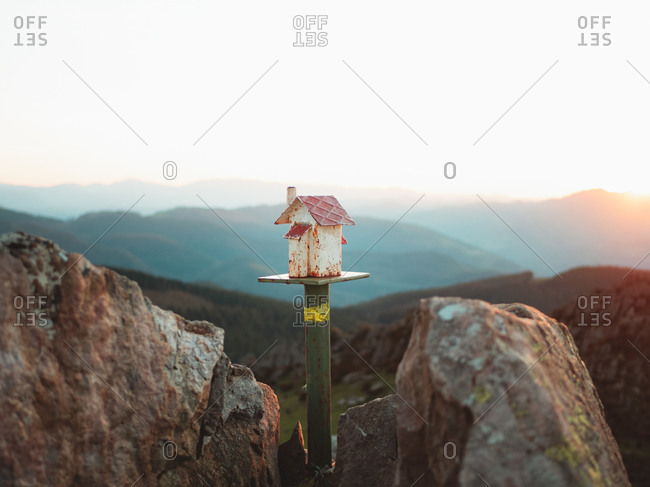 Cute decorative house between two rocks on top of Adarra mountain in Basque Country during sunset