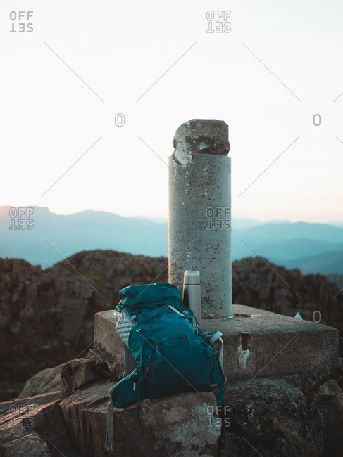 Hiking backpack and stainless steel thermal water bottle on top of Adarra mountain