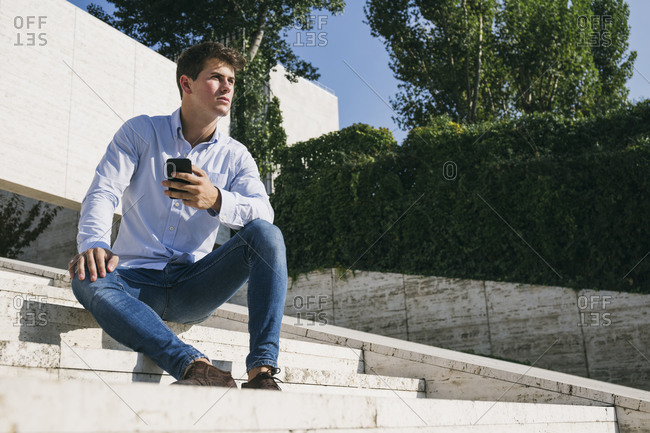 Thoughtful handsome young man sitting with smart phone on steps against trees in city during sunny day