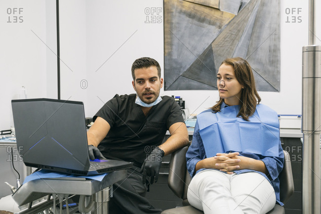Handsome male dentist explaining medical procedure to female patient on laptop in office