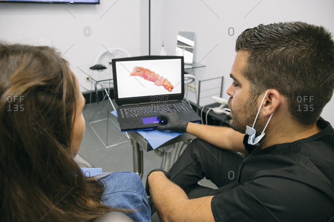 Male doctor showing picture of gums to female patient on laptop screen in clinic