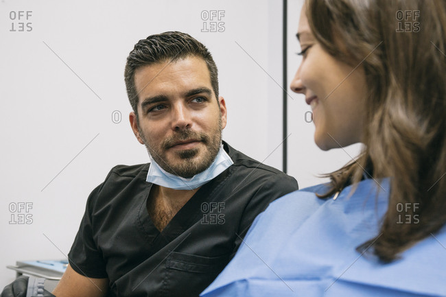 Handsome male dentist explaining dental treatment to smiling female patient in office