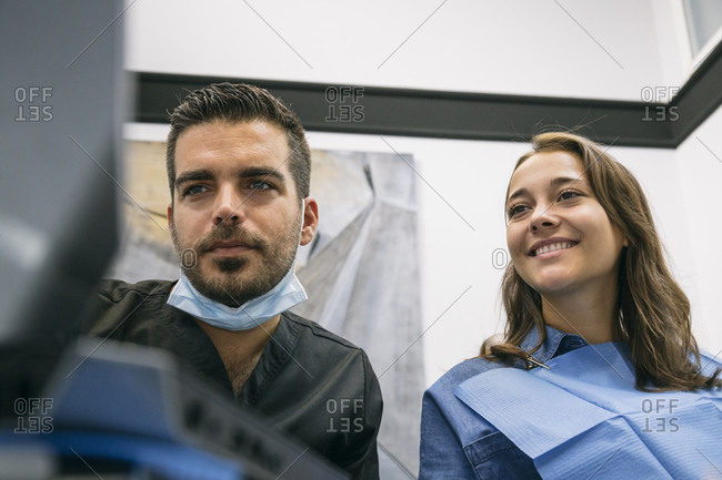 Beautiful female patient pleased with explanation of handsome male dentist on laptop at clinic