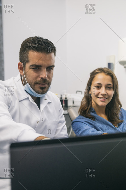 Handsome male dentist explaining medical procedure to smiling female patient over laptop in clinic