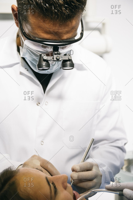 Male dentist in surgical loupes and mask examining teeth of female patient in clinic