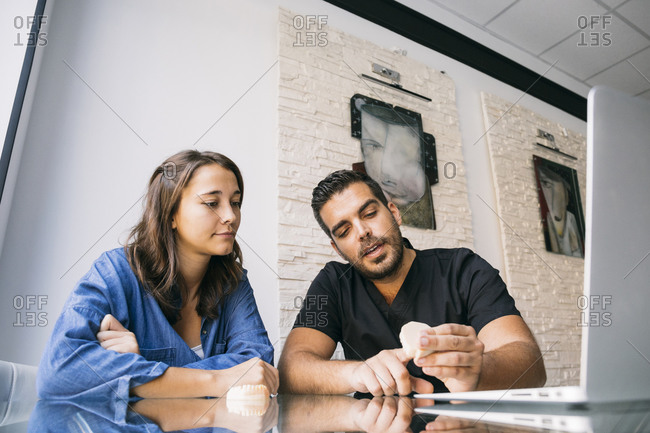 Handsome male dentist explaining female patient over gums model at desk in office