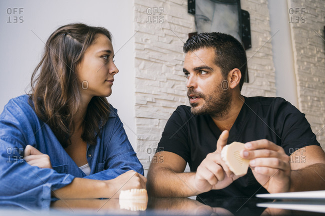 Handsome male dentist discussing with young female patient over gums model in office