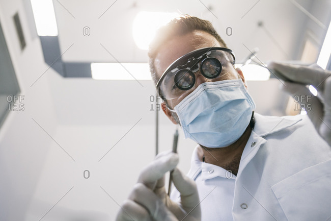 Male dentist in surgical loupes and mask with medical instruments during treatment in clinic