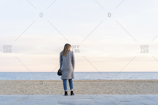 Young woman looking at sea while standing on promenade at beach enjoying sunset