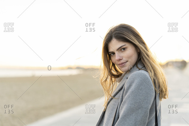 Beautiful confident woman with long brown hair standing on promenade at beach during sunset