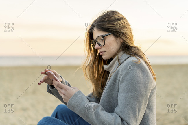 Beautiful young woman with long brown hair using smart phone at beach during sunset