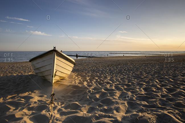 Boat left on sandy beach at dawn