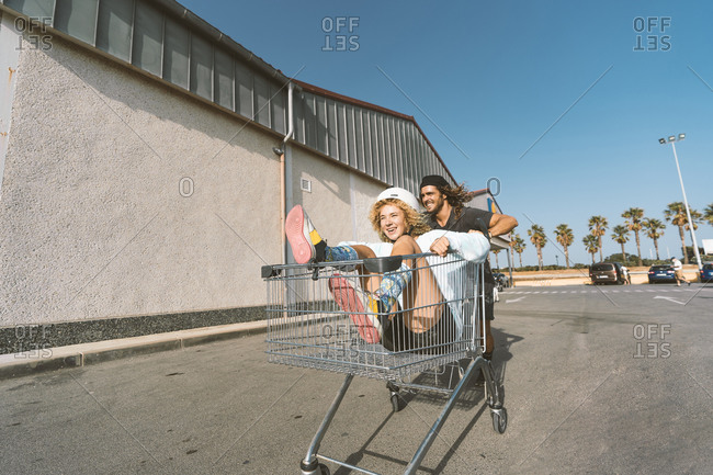 Young man pushing girlfriend sitting in shopping cart outside supermarket
