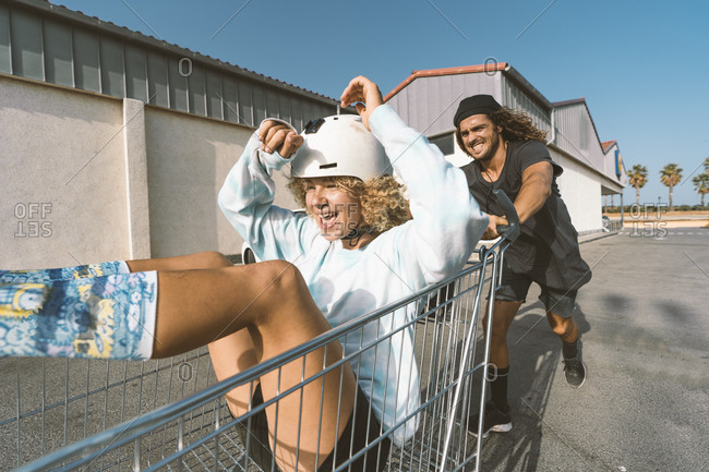 Playful young man pushing girlfriend sitting in shopping cart outside supermarket on sunny day