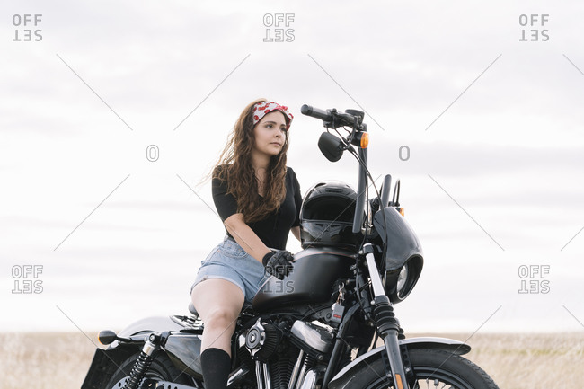 Young woman sitting on motorbike against sky