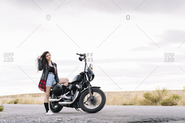 Young female biker standing on road with motorbike