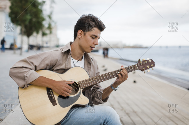 Young man playing guitar while practicing at promenade against sky