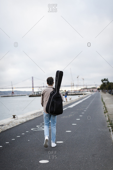 Young man with guitar walking on promenade