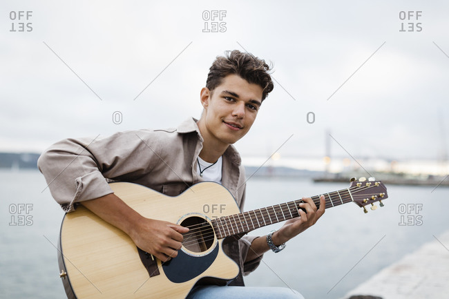 Handsome young man playing guitar while practicing at promenade against sky