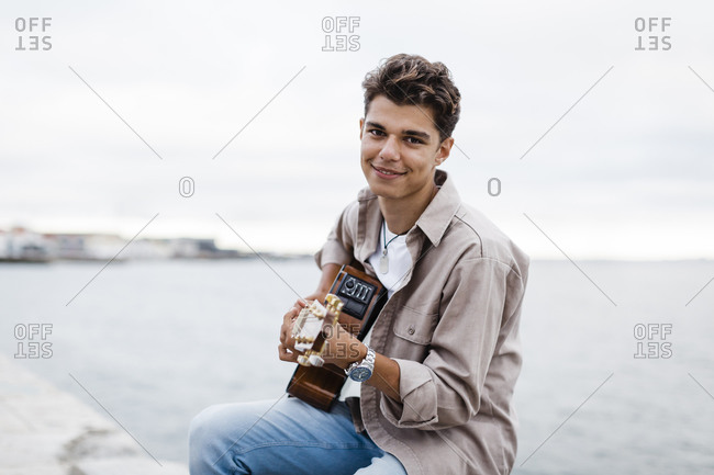 Smiling man playing guitar while practicing at promenade against sky