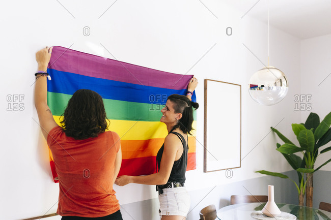 Female friends holding rainbow flag against wall at home