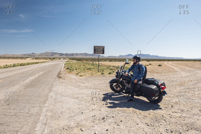 Man sitting on motorcycle parked by desert road against sky during road trip- Nevada- USA