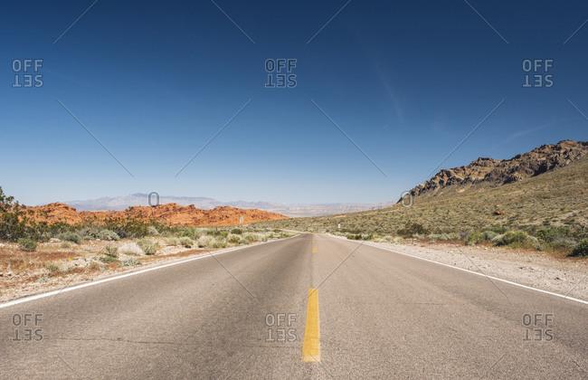 Diminishing view of empty desert road against blue sky- Nevada- USA