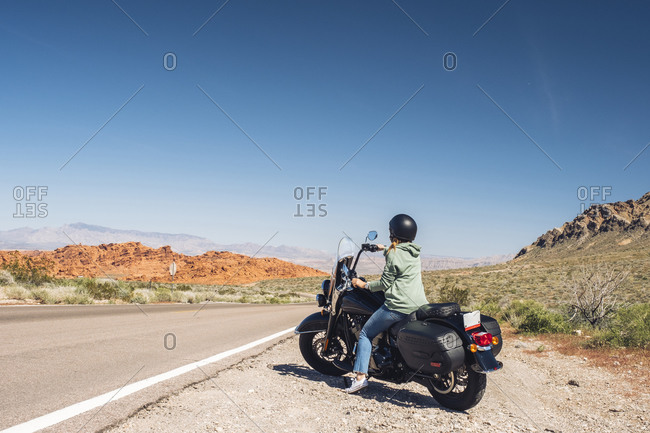 Woman riding motorcycle during summer road trip- Nevada- USA