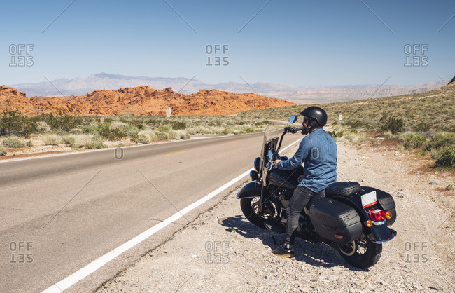 Man riding motorcycle during road trip in summer- Nevada- USA