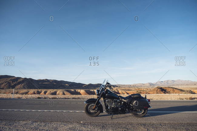Motorcycle parked on desert road against blue sky- Nevada- USA