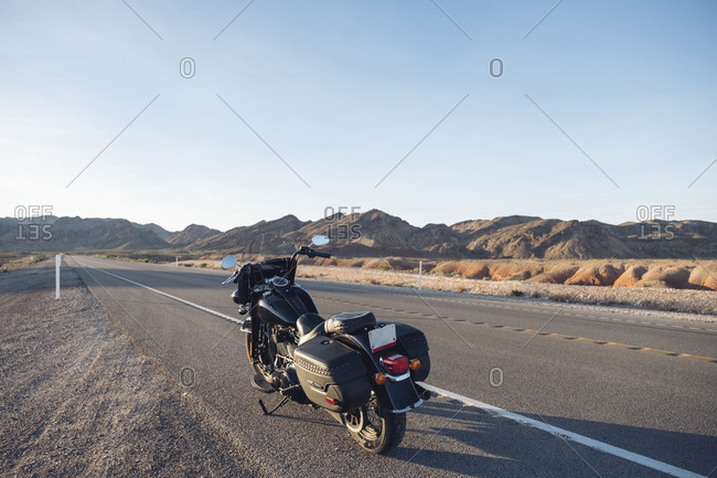Motorcycle parked on desert road against sky- Nevada- USA