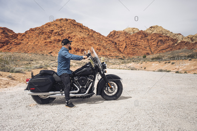 Man sitting on motorcycle at Valley of Fire State Park- Nevada- USA