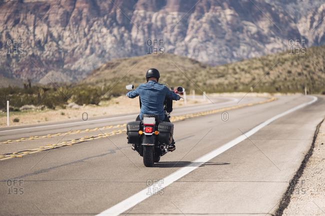 Man riding motorcycle on desert road- Nevada- USA